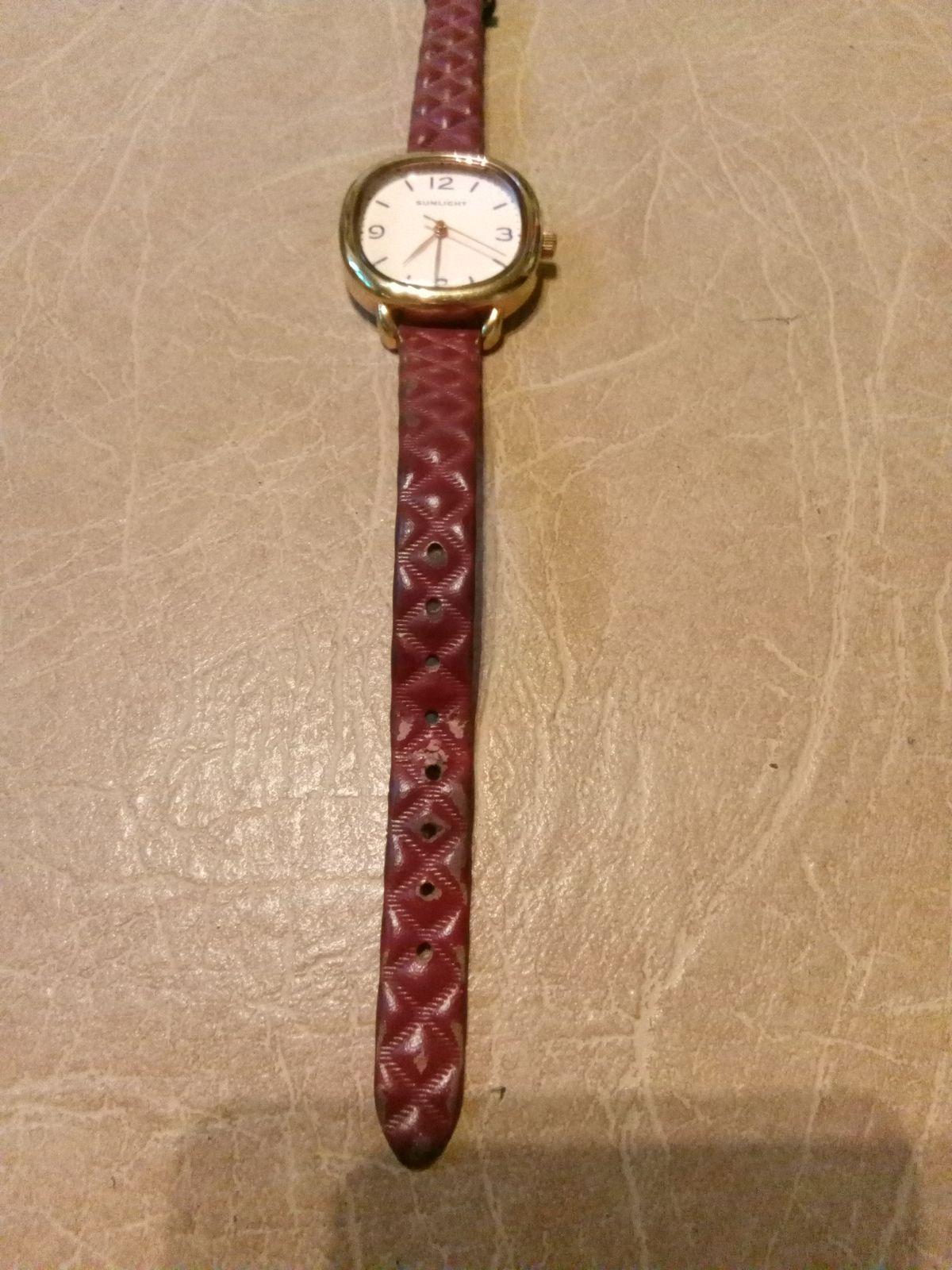 Часы с темно-красном ремешке.